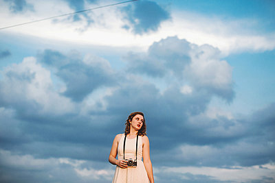 Woman against cloudy blue sky holding camera - p924m1157779 by Lena Mirisola