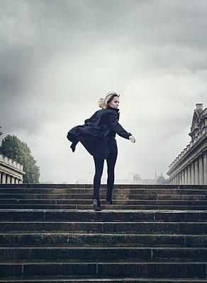 Frau in schwarzem Mantel - p984m2022596 von Mark Owen