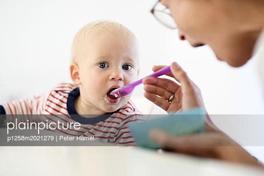Mutter füttert Kleinkind - p1258m2021279 von Peter Hamel