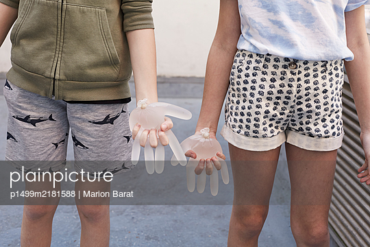 Boy and girl playing with gloves during Covid-19 quarantine - p1499m2181588 by Marion Barat