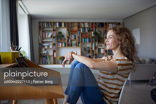Smiling woman looking away while sitting on chair by desk at home - p300m2227113 by Rainer Berg