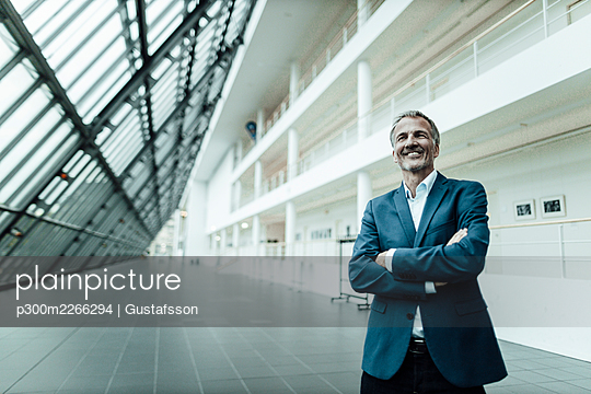 Smiling businessman with arms crossed looking away while standing in office corridor - p300m2266294 by Gustafsson