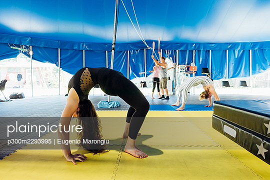 Female artist bending over backwards while practicing with athletes in background at circus - p300m2293995 by Eugenio Marongiu