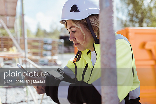Female building contractor using smart phone at construction site - p426m2296182 by Maskot