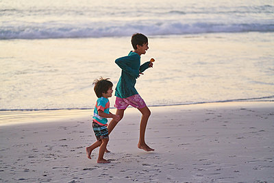Happy brothers running on ocean beach - p1023m2200924 by Trevor Adeline