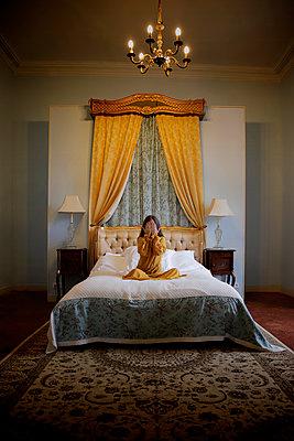 Frau im Schlafzimmer, bedeckt ihr Gesicht mit ihren Händen - p1105m2245446 von Virginie Plauchut