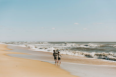 Rear view of brothers walking at shore against sky during sunny day - p1166m2034784 by Cavan Images