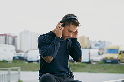 Young man with headphones on city street - p1166m2171505 by Cavan Images