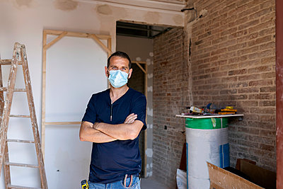 Portrait of a man wearing protective face mask in a house under construction - p300m2207039 by Valentina Barreto