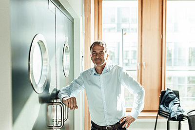 Businessman with hand on hip leaning on closed door in office - p300m2265745 by Gustafsson