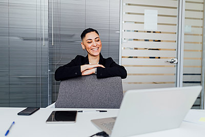 Female professional smiling during video call on laptop at office - p300m2282334 by Eugenio Marongiu
