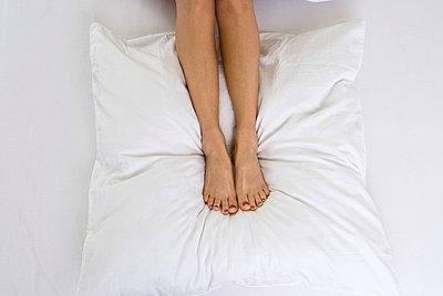 Woman's feet lying on a pillow - p3790394 by Scheller