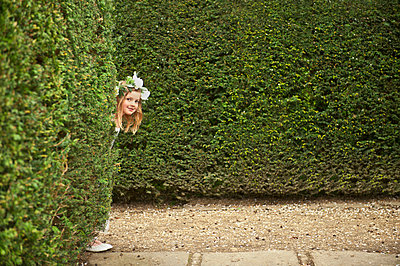 Caucasian flower girl peeking around hedges in garden - p555m1410444 by Dave and Les Jacobs