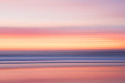 Defocused view of ocean waves on beach under sunset sky - p555m1411727 by Sam Diephuis