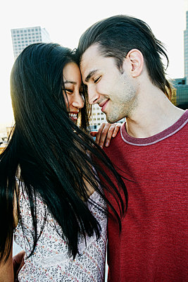 Smiling couple hugging on urban rooftop - p555m1414913 by Peathegee Inc