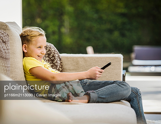 Young girl relaxed and smiling on couch using remote control at home - p1166m2113090 by Cavan Images