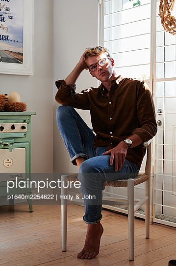 Young man with glasses on a chair, portrait - p1640m2254622 by Holly & John