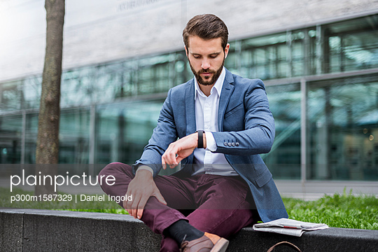 Young businessman sitting outdoors checking the time - p300m1587329 von Daniel Ingold