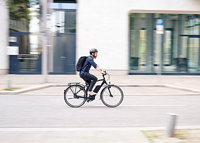 Bicycle courier riding an electric bike - p1124m2053009 by Willing-Holtz