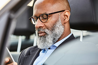 Businessman sitting in car using smartphone - p300m1417239 by Jo Kirchherr