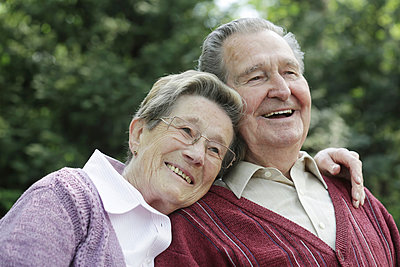 Germany, Cologne, Senior couple sitting in park, smiling - p300m2207247 by Jan Tepass
