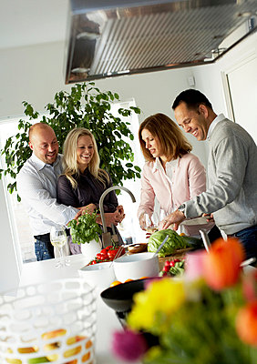 Two couples making dinner together Sweden - p31222731f by Andreas Kindler