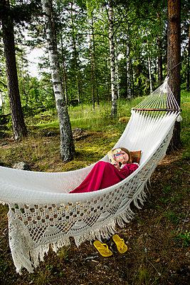 Sweden, Dalarna, Falun, Young woman lying on hammock and reading book - p352m1061643f by Lena Katarina Johansson