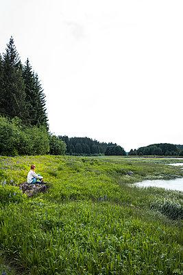 Einzelne Frau an einem Seeufer, Alaska, USA - p741m2168732 von Christof Mattes