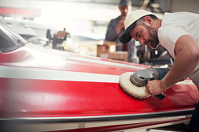 Man polishing boat in repair workshop - p924m1447063 by Zero Creatives