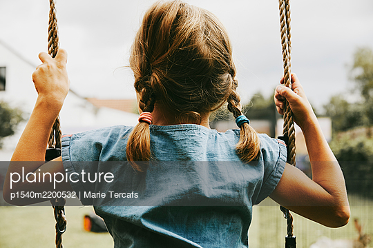 little girl with pigtails on a swing - p1540m2200532 by Marie Tercafs