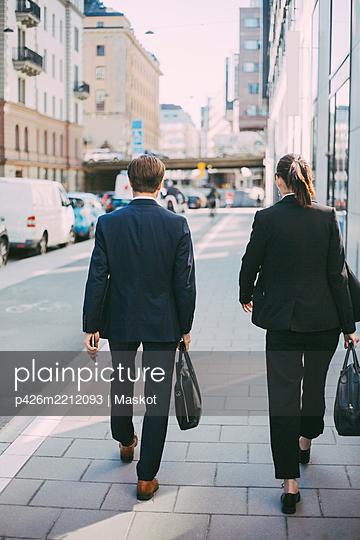 Rear view of business people walking on sidewalk - p426m2212093 by Maskot