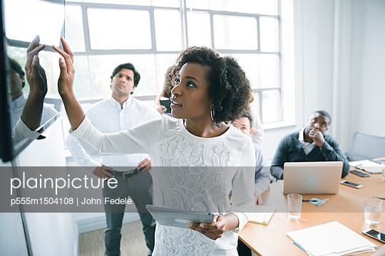 Businesswoman talking near visual screen in meeting - p555m1504108 by John Fedele