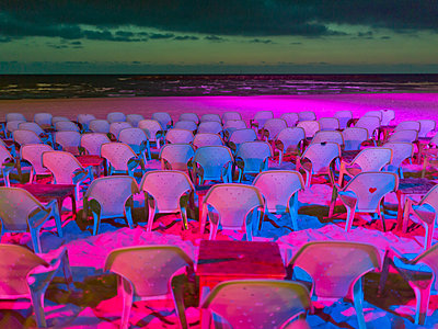 Lots of seats on the beach drenched in pink colours - p1542m2142360 by Roger Grasas
