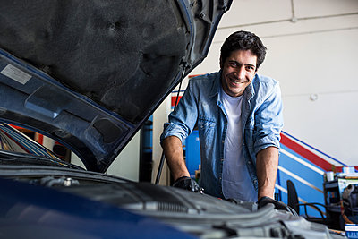 Cheerful man working in car workshop and fixing car engine with tool smiling at camera - p300m2154558 by Andrés Benitez