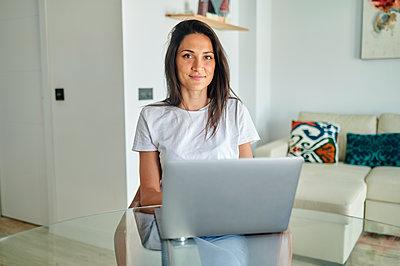 Smiling woman using laptop at home - p300m2282280 by Kiko Jimenez