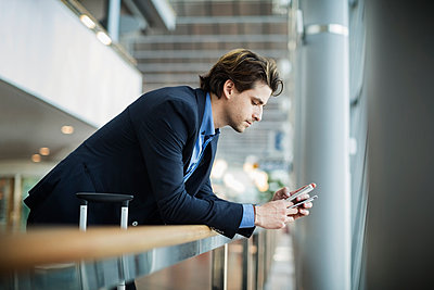 Side view of businessman using mobile phone while leaning on railing at airport - p426m1114704f by Maskot