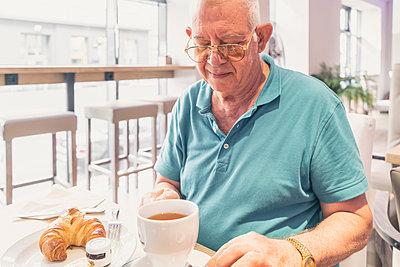 Senior man having breakfast at modern cafe - p429m2075377 by Tamboly