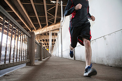 Cropped shot of young man running on city bridge - p924m896122f by heshphoto