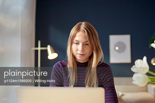 Junge Frau arbeitet am Laptop zuhause - p1124m1589205 von Willing-Holtz