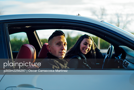 Young man staring while sitting in car with woman during sunset - p300m2256297 by Oscar Carrascosa Martinez