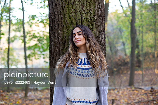 Young woman leaning against tree - p975m2222463 by Hayden Verry