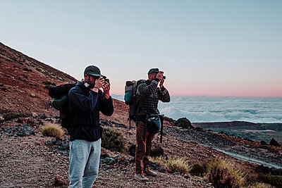 Hikers photographers taking photos in the volcano El Teide at sunset - p1166m2131164 by Cavan Images