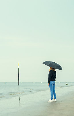Woman with umbrella by the sea - p1443m2191576 by SIMON SPITZNAGEL