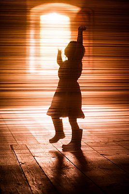 Silhouette of girl dancing on wooden floor - p312m1229397 by Peter Rutherhagen
