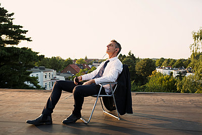 Businessman relaxing on roof - p341m2008644 by Mikesch