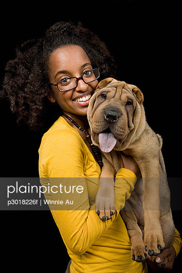 A young woman with her Shar-Pei, studio shot - p3018226f by Winnie Au