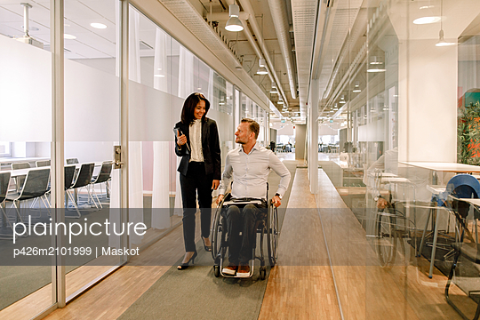 Smiling businesswoman looking at disabled colleague sitting on wheelchair in corridor at work place - p426m2101999 by Maskot