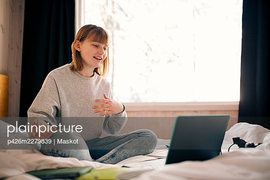 Teenage girl gesturing while attending video call during homeschooling in bedroom - p426m2279839 by Maskot