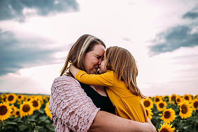 Mother and daughter embracing while standing in sunflower farm against sky - p1166m1521241 by Cavan Images