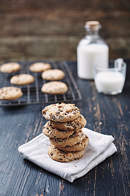 Stack of chocolate chip cookies with milk in background on wooden table - p1166m1577844 by Cavan Images
